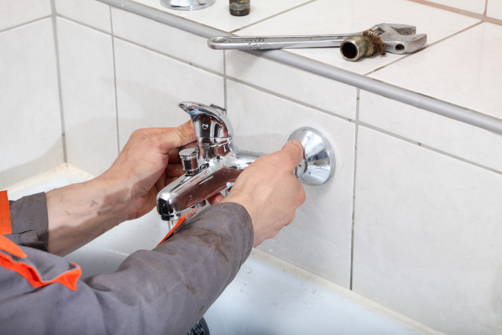 Plumber hands fixing water tap with spanner