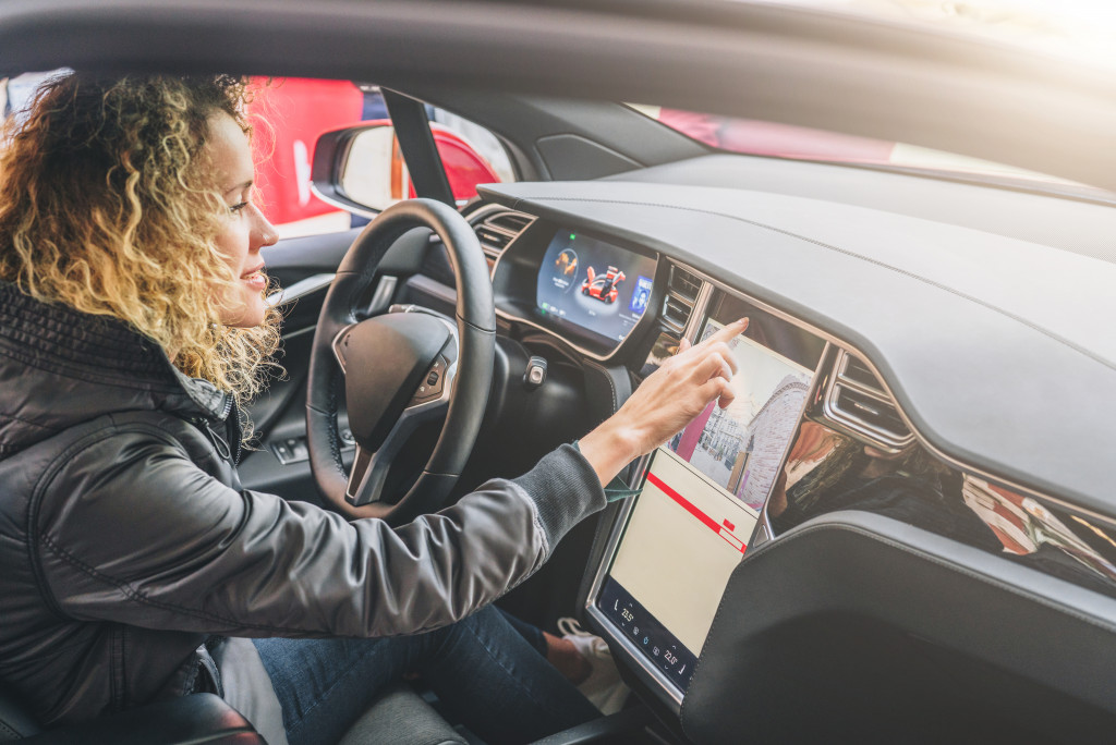 Young woman sits behind wheel in car and uses an electronic dashboard, tablet computer