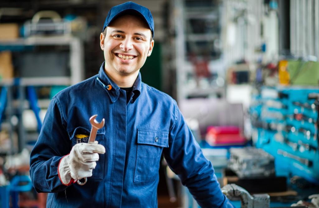 Auto mechanic smiling in his garage