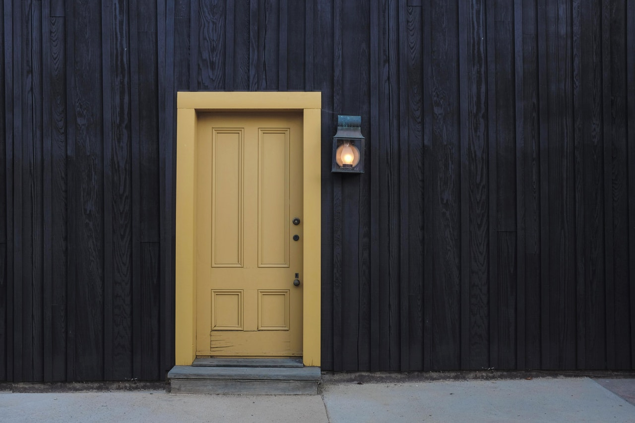 yellow door on a black wall