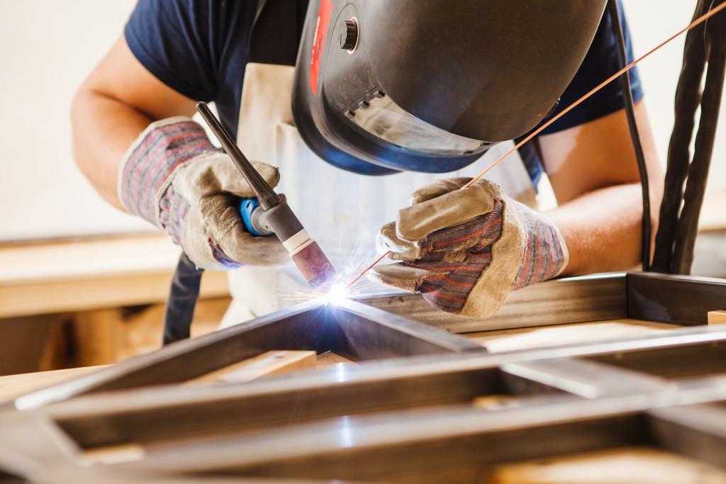 man welding metals